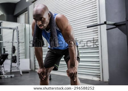 Young Bodybuilder looking exhausted in the cross gym - stock photo