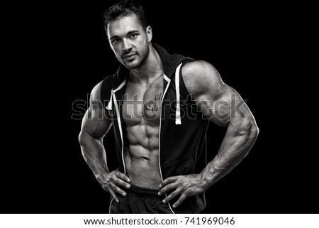 Young bodybuilder posing in front of black background