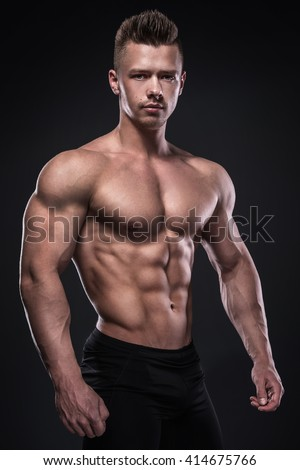 Young bodybuilder showing his muscles in studio - stock photo