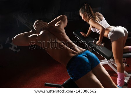 Young bodybuilder training his muscular back and woman working on her prelum on the bench in gym - stock photo