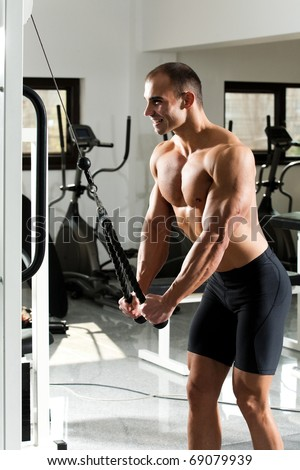 young bodybuilder training in the gym - cable rope triceps extension - stock photo