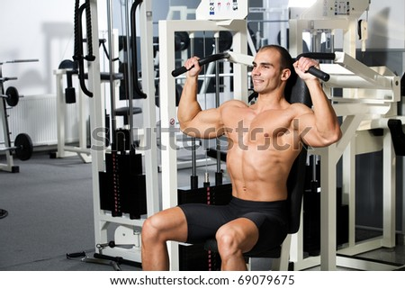 young bodybuilder training in the gym - machine shoulder press, start position - stock photo