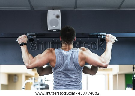 young bodybuilder training in the gym.  The man is tightened on the bar. - stock photo