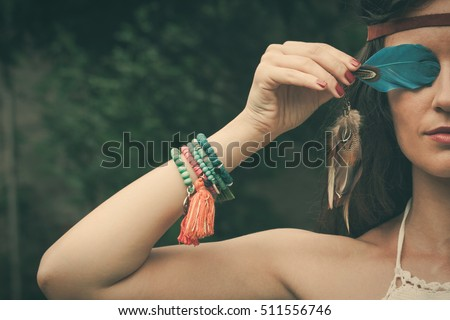 young bohemian fashion style woman with feather portrait closeup