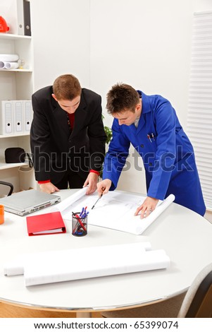 Young boss and employee surveying projects in office - stock photo