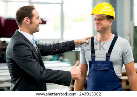 young boss is lauding worker in factory - stock photo