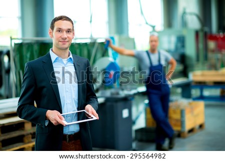 young boss with worker in the background in his factory