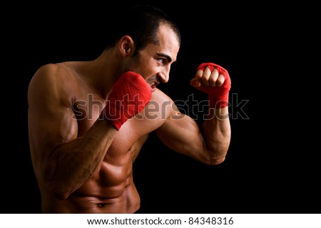 Young Boxer fighter over black background
