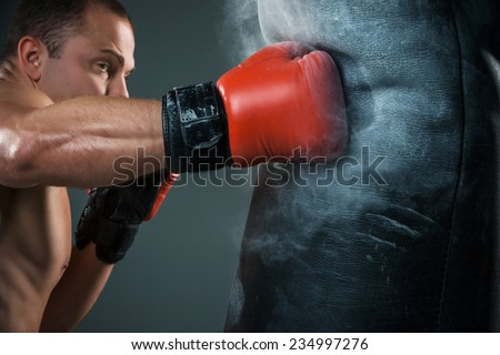 Young boxer in red gloves boxing over black background - stock photo