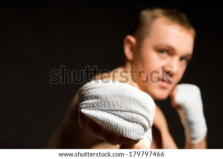 Young boxer throwing a powerful punch in the direction of the camera with a bandaged fist with focus to his hand - stock photo