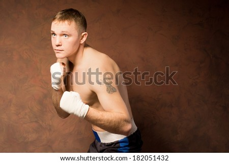 Young boxer training before a match standing with his bandaged fists raised as he keeps a watchful eye on his opponent, against a brown wall with copyspace - stock photo