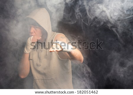 Young boxer working out in a smoky room in a hooded grey top standing with his bandaged hands raised waiting and watching - stock photo