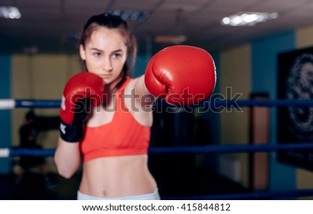 young boxing girl doing exercises on a boxing ring