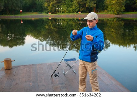 Young boy adjusts float rods on dock at river early morning. - stock photo