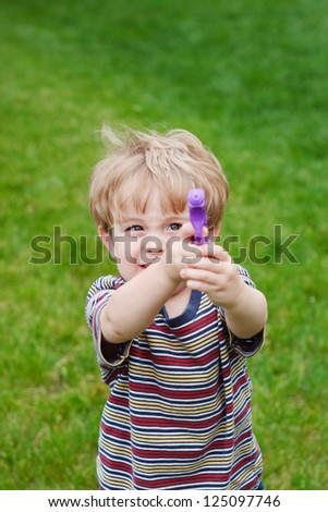 Young boy aiming a  water gun - stock photo