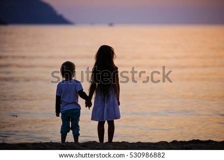 Young boy and girl holding hands while standing on beach at sunset