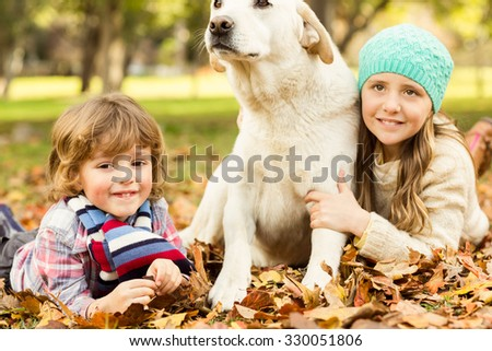 Young boy and girl lying with their dog in leaves on an autumns day - stock photo