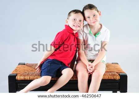 Young boy and girl on bench together - stock photo