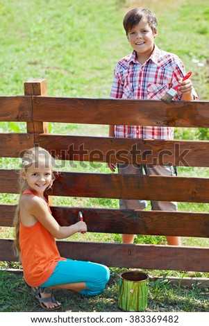 Young boy and girl painting a wooden fence on a sunny summer day - stock photo