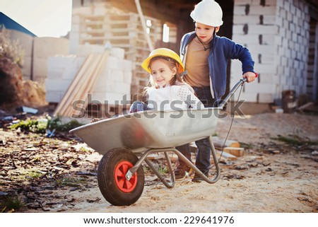 young boy and girl playing on construction site - stock photo