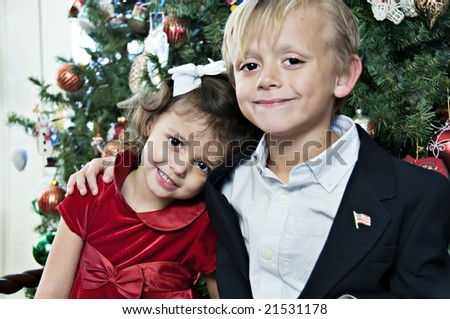 Young boy and girl posing by the Christmas Tree