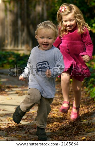 Young boy and girl running in autumn leaves - stock photo