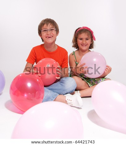 Young boy and girl with colorful balloons - stock photo