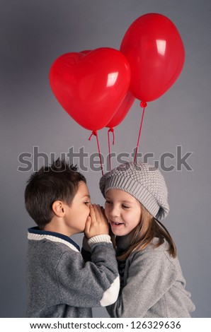 Young boy and girl with red heart balloons on grey background. Valentines day concept. - stock photo