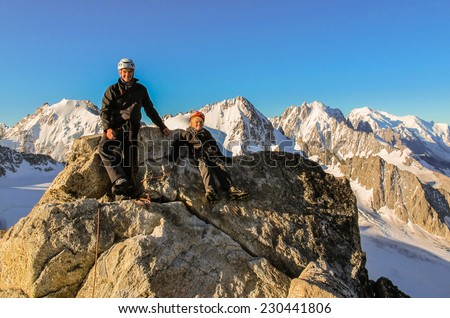 Young boy and his father on the summit of Aiguille du Tour in the alps just after dawn. - stock photo