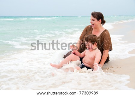 Young boy and his mom play in the surf at beach. - stock photo