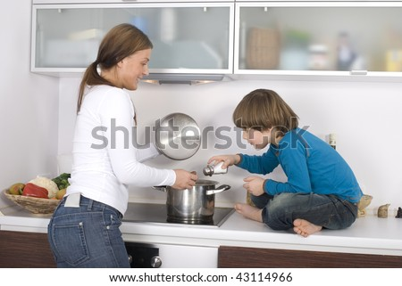 Young boy and his mother are standing over the stove cooking dinner. - stock photo