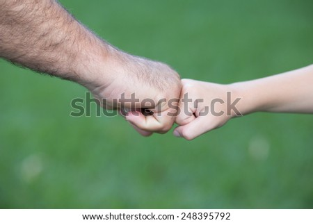 Young boy and man are fist bumping - stock photo