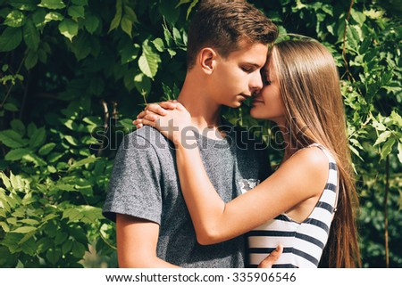 Young boy and pretty girl couple in park, happy together, embracing - stock photo