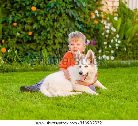 young boy and White Swiss Shepherd`s puppy