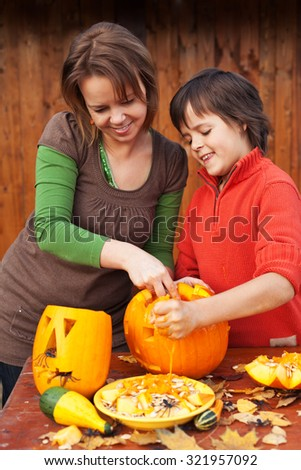Young boy and woman carving a jack-o-lantern - preparing for halloween - stock photo