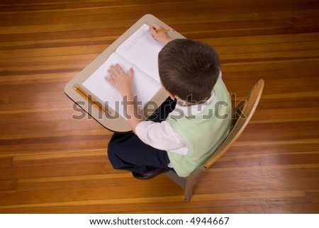 Young boy at school desk writing with book and pencils isolated over a wood floor - stock photo