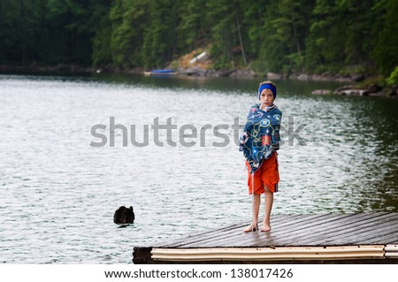 young boy at the lake wearing a swim band to protect his ears - stock photo