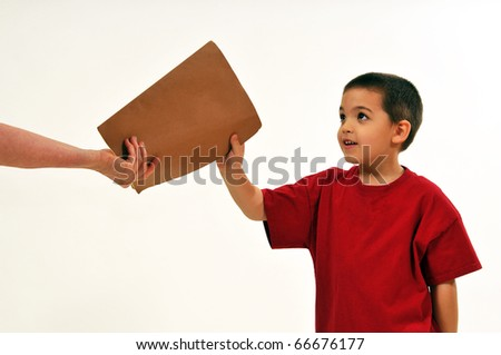 Young boy being handed a folder, smiling as he receives a good report. - stock photo