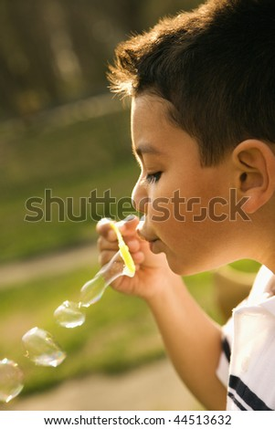 Young boy blowing bubbles outside. Vertically framed shot. - stock photo