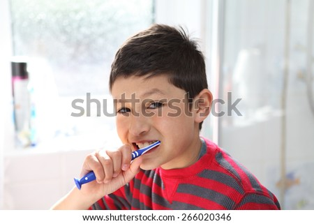 Young boy brushing his teeth - with copy space
