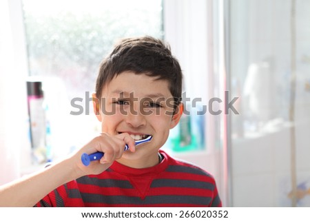 Young boy brushing his teeth - with copy space - stock photo