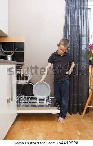 Young Boy by the Dishwasher with a plate - stock photo