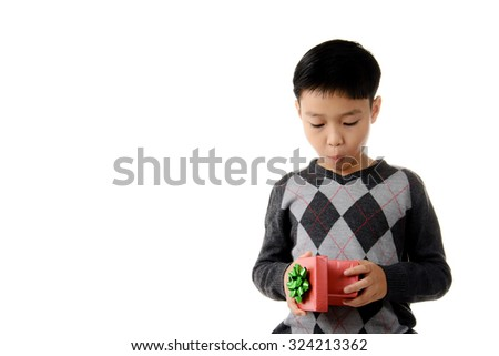 Young boy carry and look inside gift box in his hand. Christmas and new year concept. - stock photo