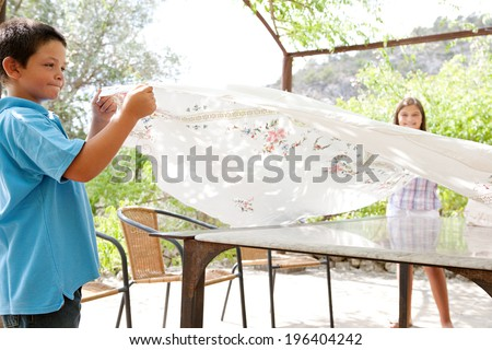 Young boy child and sister girl preparing a summer lunch outdoors table throwing a luxury embroidered table cloth over and getting ready for eating in a holiday villa home garden. Outdoors lifestyle.