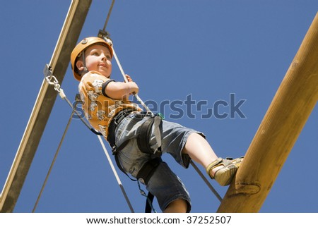 Young boy climbing  a log with sky in background