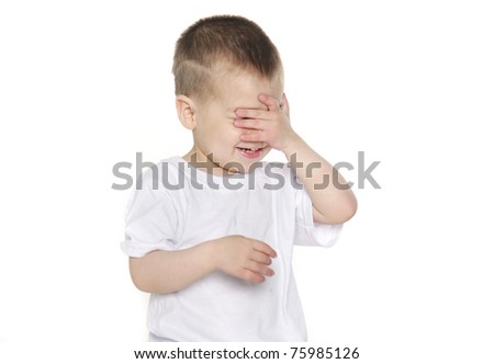 young boy closing hid eyes by hand over white