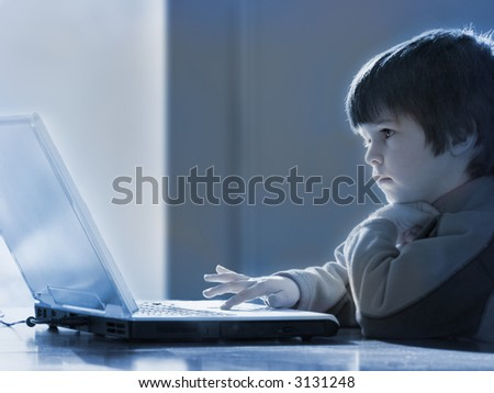 young boy concentrates on laptop computer - blue tone/b&w - stock photo