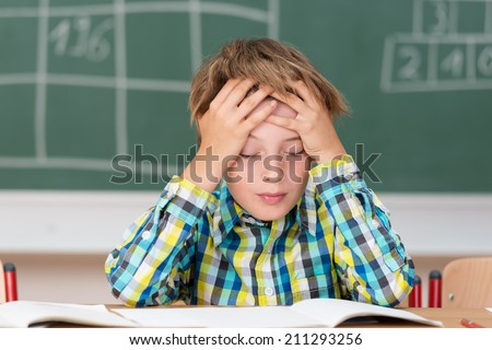 Young boy concentrating on his schoolwork sitting at his desk in the classroom with his head in his hands reading his class notes - stock photo