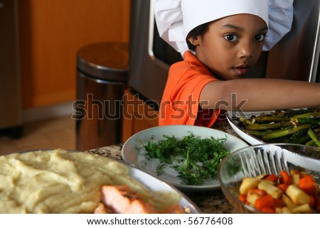 Young boy cooking a complete dinner meal. - stock photo