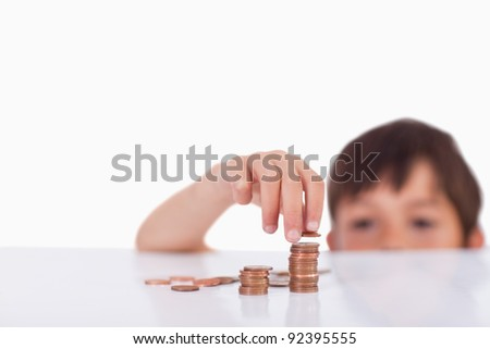 Young boy counting his change against a white background